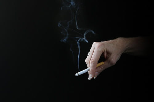 a hand holds a cigarette against a black background as smoke wafts into the air