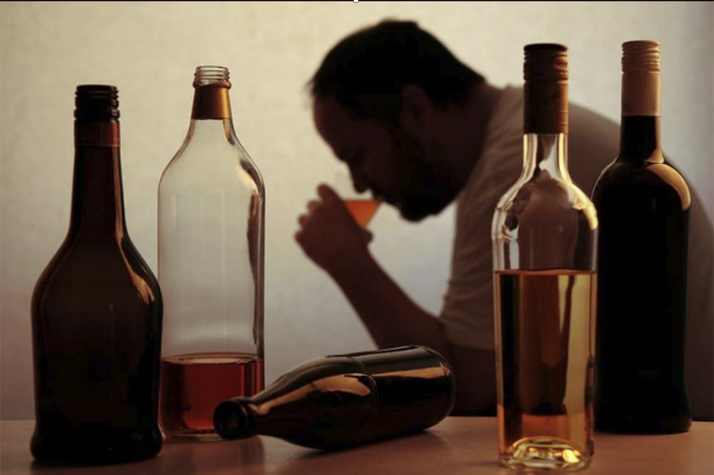 A man in silhouette drinks, framed by alcohol bottles