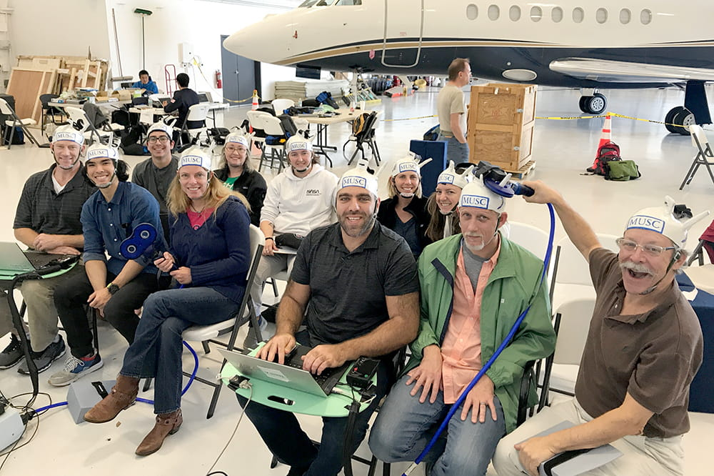 the team sits in an airplane hangar, with a private plane in the background, with the handcrafted helmets on their heads