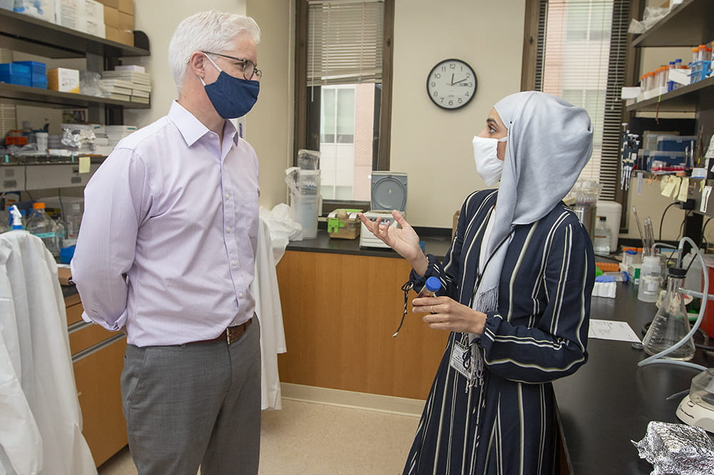 Dr. Christopher Cowan (left)  speaking with  Dr. Ahlem Assali (right) in the laboratory