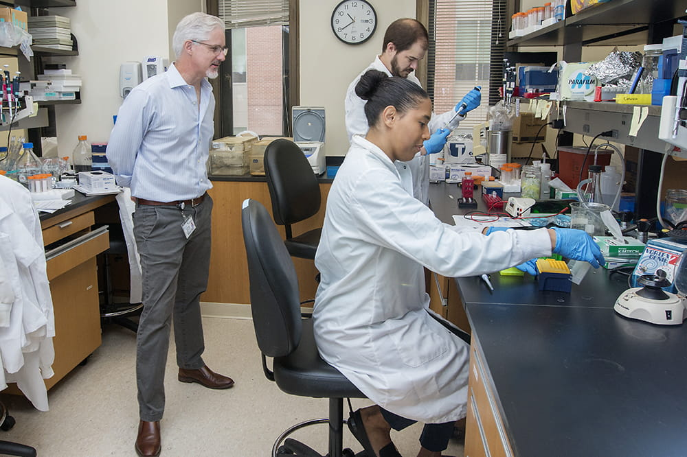 Chris Cowan, chairman of the Department of Neuroscience, observes Adam Harrington and Catherine Bridges at work. Harrington and Bridges are joint lead authors of a new paper about MEF2C haploinsufficiency syndrome.